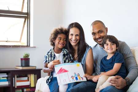 Proud parents showing family painting of son sitting on sofa at home. Smiling mother and father with children's drawing of a new home. Black little boy with his family at home showing a painting of a happy multiethnic family.