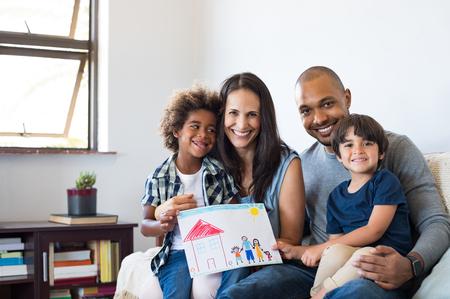 Stolze Eltern zeigen Familie Malerei von Sohn sitzen auf Sofa zu Hause. Lächelnde Mutter und Vater mit Kindern Zeichnung eines neuen Hauses. Schwarzer kleiner Junge mit seiner Familie zu Hause zeigt ein Gemälde einer glücklichen multiethnischen Familie.