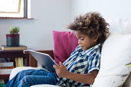 Little african boy sitting on sofa and playing game on digital tablet. Portrait of a young black child at home watching cartoon on the laptop. Modern kid and education technology. Banco de Imagens