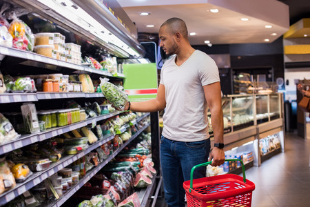 Jonge Afrikaanse mens het kopen groenten in kruidenierswinkelsectie bij supermarkt. De zwarte mens kiest groenten in de supermarkt terwijl kruidenierswinkelmand houdt. Mens die veggies bij supermarkt winkelt. Stockfoto