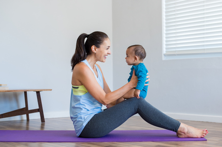 Happy woman playing with 6 months baby while doing yoga. Smiling mother doing yoga exercise with multiethnic baby while sitting on yoga mat. Little cute boy sitting on mother knee playing at home. Stock Photo