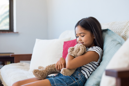 Sonriente niña sentada en el sofá y abrazando a su osito de peluche. Niña linda asiática abrazando juguete de peluche en casa. Niño femenino multiétnico que juega con el oso del juguete de la felpa en el sofá.
