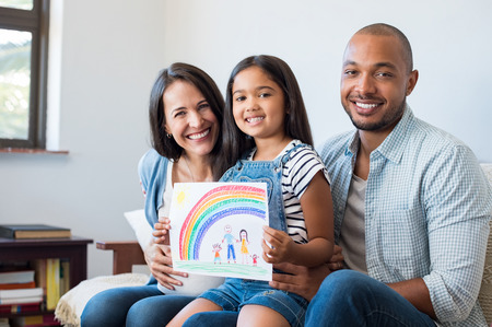Smiling daughter showing painting of happy family with parents and beautiful rainbow. Happy child showing drawing of family with little brother. Cheerful pregnant woman with her family looking at camera.