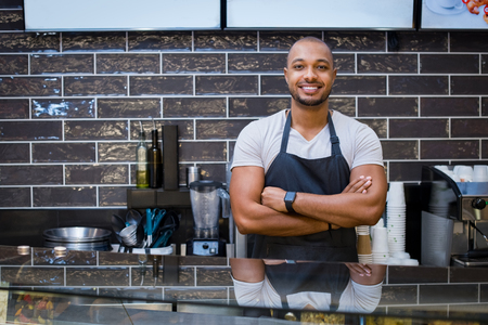 profession: Portrait of a smiling african waiter standing in the cafeteria with crossed arms. Confident young man with apron in coffee shop looking at camera. Handsome black guy working in a coffeeshop.