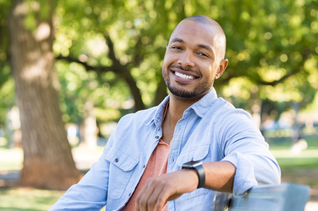 real: Young african man relaxing at park in a summer day. Happy black cheerful guy feeling good and sitting on bench at park. Smiling american man looking at camera outdoor.