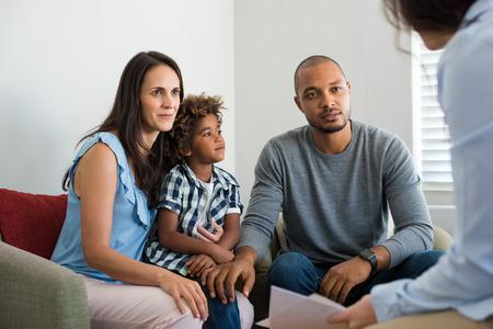 Ernstig paar met zoon in een diep gesprek met familieadviseur. Multi-etnische ouders praten over adoptie met hun counsellor. Familie bij het financiële planningsoverleg. Stockfoto