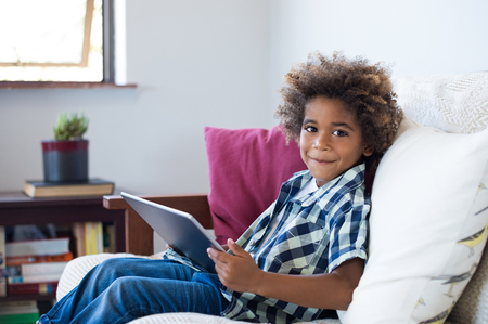 Young african child sitting on sofa playing game on a digital tablet. Cheerful little black boy holding digital tablet at home. Happy smiling kid using digital tablet and looking at camera. Фото со стока