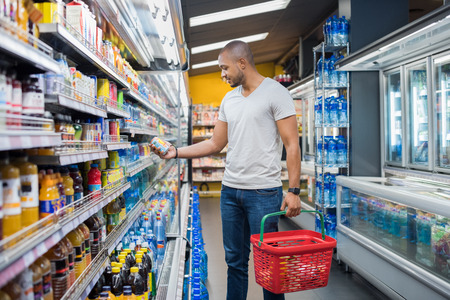 African man shopping in beverage section at supermarket. Black man doing shopping at market while buying cold drink. Handsome guy holding shopping basket reading nutritional values of product.