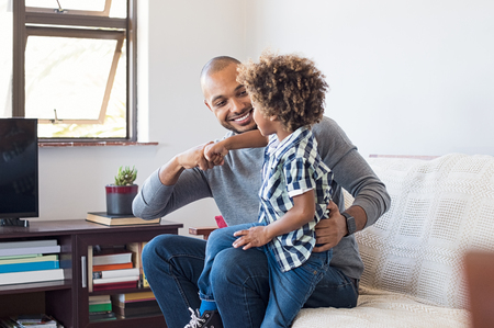 Happy african father and son punching knuckles. Young black man and little boy playing with each other at home in living room. Happy dad and smiling child playing by punch their fists.