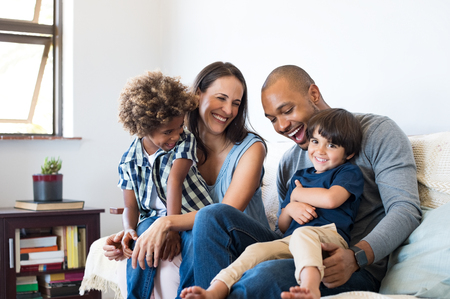 Happy multiethnic family sitting on sofa laughing together. Cheerful parents playing with their sons at home. Black father tickles his little boy while the mother and the brother smile.