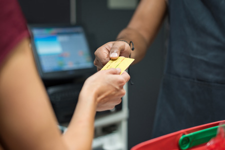 supermarket: Close up of customer�s hand giving credit card to cashier at checkout. Woman using credit card to pay at supermarket. Woman paying with debit card at cash register.