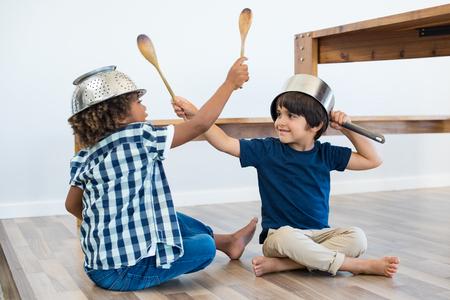 Weinig schattige jongens die op de vloer vechten met keukengerei. Gelukkige multiethnische broers dragen een kom en kuilen als helm en houten lepels als zwaard voor spel. Glimlachende kinderen vrienden thuis spelen.