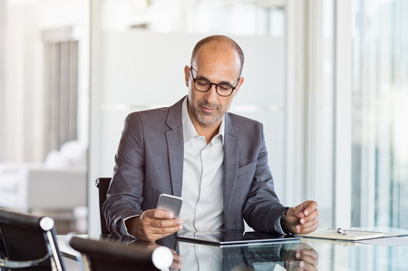 technology: Mature business man in formal clothing wearing spectacles using mobile phone. Serious businessman using smartphone and digital tablet at work. Manager in suit using cellphone in a modern office.