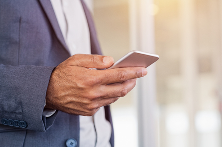 technology: Close up of a man using mobile smart phone. Close up hand of businessman in formals typing on smartphone. Detail of businessman holding cellphone while checking emails.