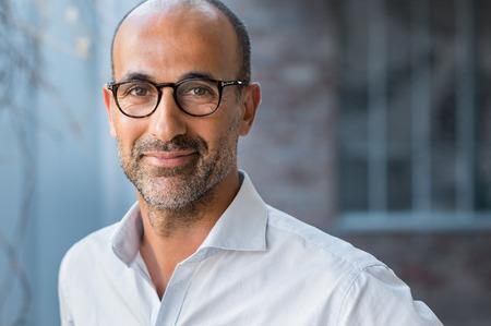 Portret van gelukkige volwassen man die bril draagt en camera buiten kijkt. Man met baard en bril voelt zich ervan overtuigd. Close-up gezicht van Spaanse zaken man lachend. Stockfoto