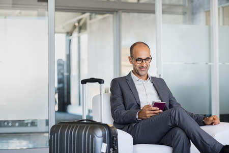 technology: Mature businessman using mobile phone at the airport in the waiting room. Business man typing on smartphone in lounge area. Portrait of latin man sitting and holding passport with luggage.