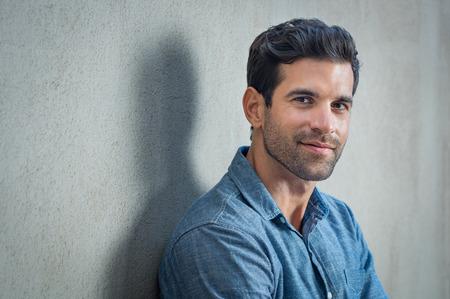 Handsome junge Mann posiert auf grauem Hintergrund. Porträt von zufriedenen Geschäftsmann gegen graue Wand. Close up Gesicht der modischen lateinischen Mann auf grauem Hintergrund.