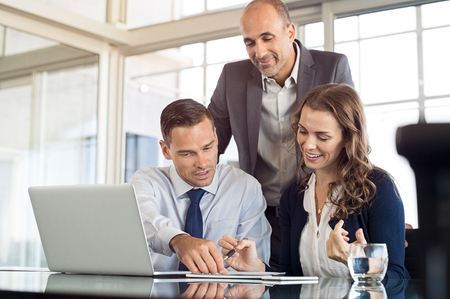 Group of colleagues working in a meeting room. Happy business team discussing together at office with laptop and documents. Business people brainstorming on next sales strategy in a modern office.