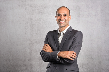 Portrait of happy mature businessman smiling on grey background. Successful senior leader in formal standing against grey wall with crossed arms. Satisfied hispanic man feeling proud and looking at camera.