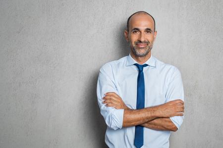 Gelukkige rijpe zakenman in blauwe overhemd en band die camera bekijken. Portret van glimlachende en tevreden Spaanse bedrijfsmens met gekruiste die wapens over grijze achtergrond met exemplaarruimte wordt geïsoleerd. Succesvolle hogere mens die zich op grijze muur bevindt.