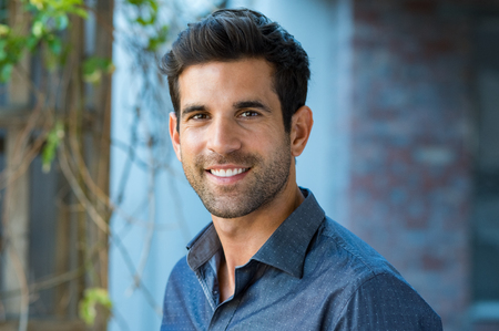 Handsome mid adult man smiling and looking at camera. Portrait of happy young casual man. Close up portrait of hispanic guy standing outdoor.