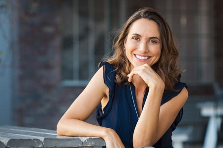 Retrato de la hermosa mujer madura sentado en la cafetería. Feliz mujer hispana sonriente sentado en un banco en la cafetería al aire libre mirando la cámara. Retrato de la mujer despreocupada que se relaja en banco. Foto de archivo
