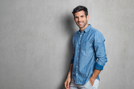 Happy smiling man leaning against grey wall. Portrait of proud mid man isolated on grey background. Young casual hispanic man against grey wall looking at camera. Banque d'images