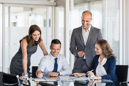 Joyeuse équipe lors d?une réunion pour discuter de stratégies dans une salle de conférence moderne. Les gens d'affaires discutant des avantages de la coentreprise sur tablette numérique. Hommes et femme d'affaires travaillant ensemble.