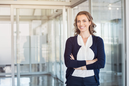 Portrait of mature beautiful business woman in the office looking at camera. Business executive standing in modern office with big smile. Cheerful mid businesswoman with copy space.