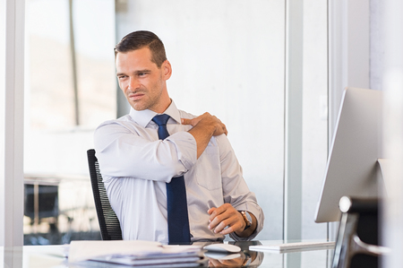 젊은 사업가 어깨 고통에서 고통을 직장. 어깨를 잡고 작업 완료 후 스트레칭 사업가. 스트레스 사업가 긴 시간의 작업 후 허리 통증이있다.