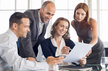 Happy businesspeople working together in new deal. Group of formal businessmen and businesswomen analysing reports and documents in a meeting. Brainstorming of business team.