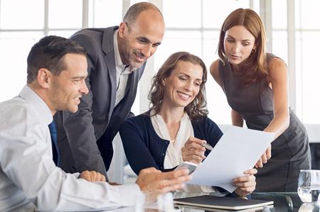 Des hommes d'affaires heureux travaillent ensemble dans un nouvel accord. Groupe d'hommes d'affaires formels et femmes d'affaires analysant des rapports et des documents lors d'une réunion. Brainstorming of business team. Banque d'images - 83142187