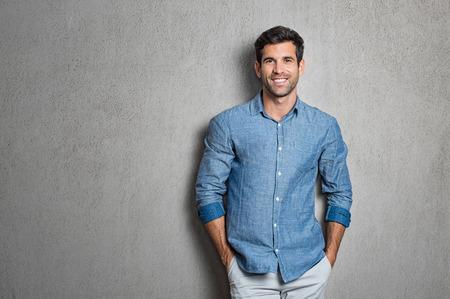 Portrait d'un beau jeune homme souriant sur fond gris avec espace de copie. Mec latin souriant avec les mains dans les poches en chemise bleue debout et s'appuyant sur le mur. Homme hispanique réussi à regarder la caméra. Banque d'images - 83142224