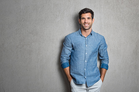 Portrait of a handsome young man smiling against grey background with copy space. Smiling latin guy with hands in pocket in blue shirt standing and leaning on wall. Successful hispanic man looking at camera. Archivio Fotografico