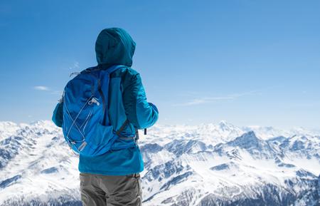 Rear view of sporty hiker man looking snowy landscape from mountain peak. Banco de Imagens