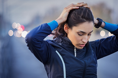 Young runner taking a break from jogging while holding head and breathing outdoor.