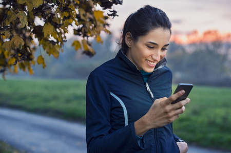 Young athlete looking at phone and smiling at park during sunset.