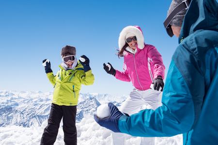 Gelukkige zoon en glimlachende moeder spelen in de sneeuw met vader.