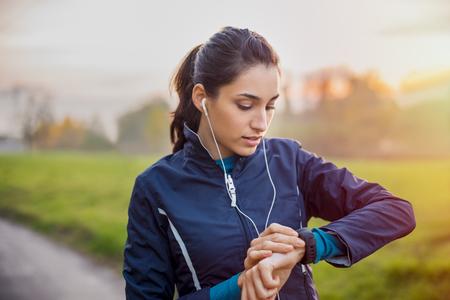 Jeune athlète écoutant de la musique lors d'une séance d'entraînement dans le parc et en ajustant la montre intelligente. Banque d'images - 83992307
