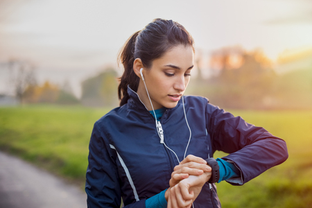 Young athlete listening to music during workout at park and adjusting smart watch. Banque d'images