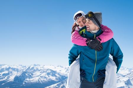 彼の笑顔のガール フレンドにおんぶを与える山で幸せな男。