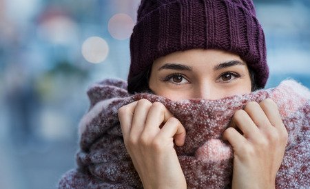 Winter portrait of young beautiful woman covering face with woolen scarf. Closeup of happy girl feeling cold outdoor in the city. Young woman holding scarf and looking at camera. Stok Fotoğraf