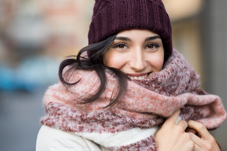 Closeup face of a young happy woman enjoying winter wearing scarf and cap. Stock Photo