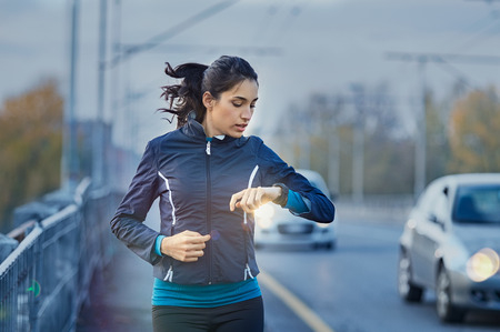 Young fitness woman runner checking time from smart watch. Banco de Imagens
