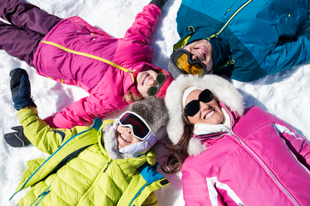 Happy young family lie on snow in winter holiday and looking at camera. 스톡 콘텐츠