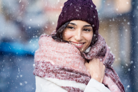 Smiling woman wearing wool bonnet and scarf in a winter cold day. Stockfoto