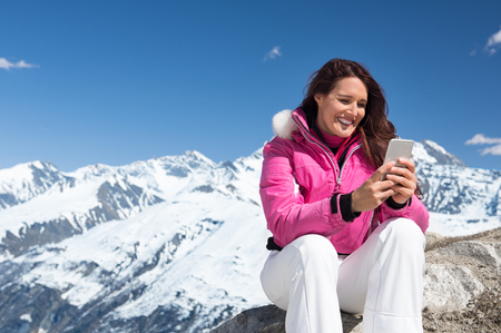 Happy woman using smartphone while sitting on rock with snowy mountains in background.