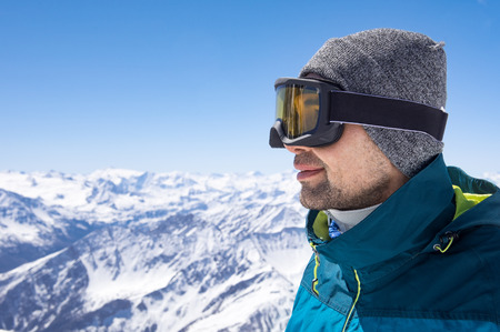 Portrait of man wearing ski glasses and cap while looking the snowy mountains. Closeup face of sporty guy contemplate the snowy. Satisfied skier smiling and wearing ski mask in mountains. Stock Photo