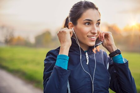 Young athlete adjusting jacket while listening to music at park.