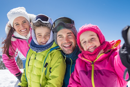 Happy family taking selfie in snowy mountain during winter holiday.